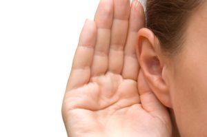 Hand achter oor als gebaar van ik luister naar je