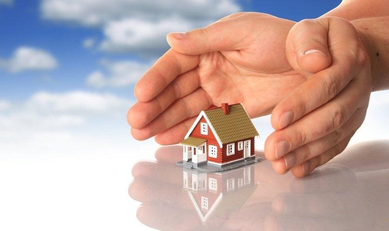 2 handen beschermend om een speelgoed huisje